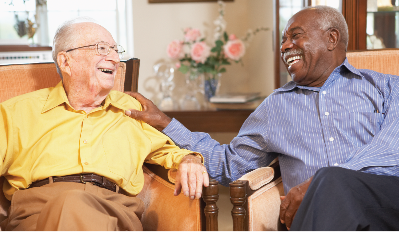 Two senior men sitting in chairs and smiling while talking to eachother